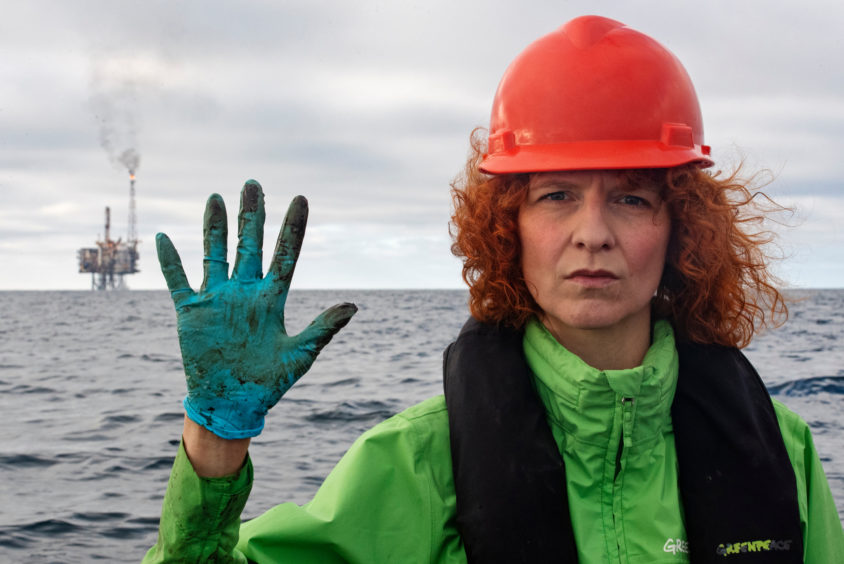 Greenpeace Germany Oceans campaigner Sandra Schoettner shows her gloves with the Andrew platform in the background.  © Marten van Dijl / Greenpeace