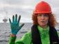 Greenpeace Germany Oceans campaigner Sandra Schoettner shows her gloves with the Andrew platform in the background.  © Marten van Dijl / Greenpeace