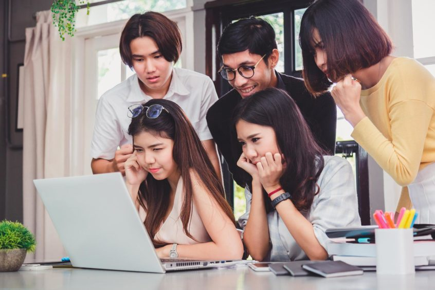 Group of five young euphoric students watching exam results in a laptop in a table of an university campus bar.; Shutterstock ID 720895372; Purchase Order: -