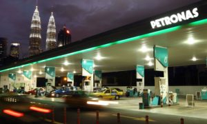 Vehicles move past a Petroliam Nasional Bhd. (Petronas) gas station as the Petronas Twin Towers, background third left, stand at night in Kuala Lumpur, Malaysia, on Tuesday, March 5, 2013. Photographer: Goh Seng Chong/Bloomberg