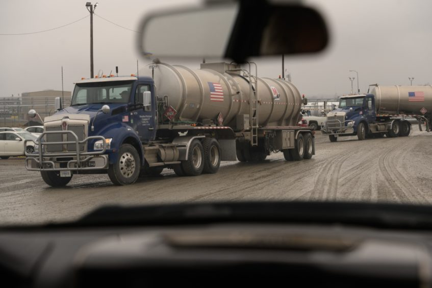 """Trucks leave the MarkWest Energy plant in Cadiz, Ohio, U.S., on Tuesday, Feb. 25, 2020. Many Rust Belt voters rely on oil and natural gas jobs and they're wary of Democratic proposals, such as the """"Green New Deal,"""" that push for """"net-zero emissions"""" and would effectively put coal and other fossil fuels out of business. Photographer: Justin Merriman/Bloomberg"""