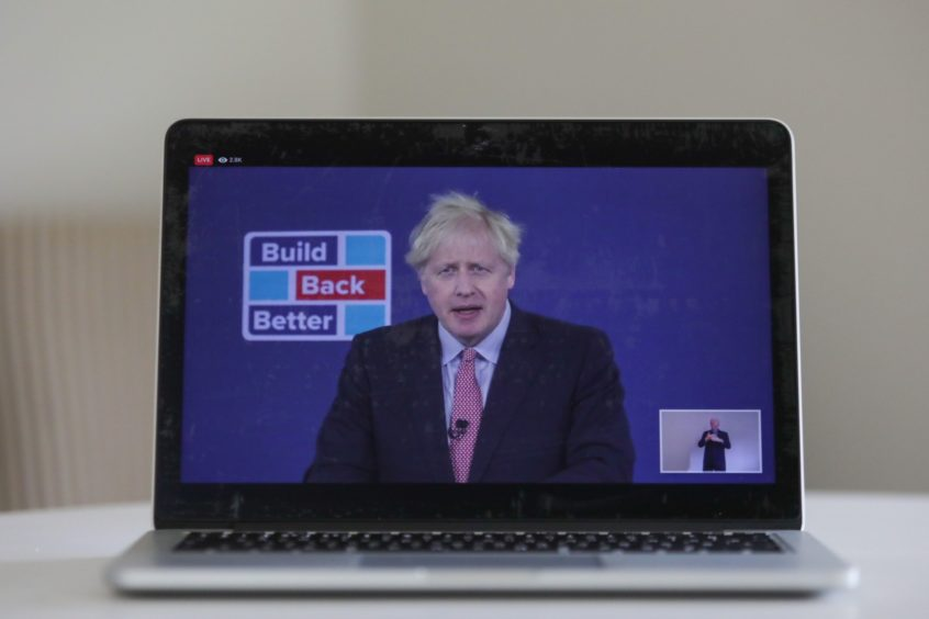 """A laptop displays a live broadcast by U.K. Prime Minster Boris Johnson delivering his leader's keynote speech at the Conservative Party virtual conference in this arranged photograph in Danbury, U.K., on Tuesday, Oct. 6, 2020. Johnson will commit to boosting U.K. offshore wind power as part of his delayed plan for a """"green industrial revolution"""" as he seeks to get his stalled domestic agenda back on course. Photographer: Chris Ratcliffe/Bloomberg"""