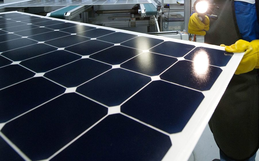 An employee of SunPower Corp. trims the edges and checks solar panels at the SunPower Corp. module manufacturing plant at Flextronics in Milpitas, California, U.S., on Wednesday, Aug. 24, 2011.