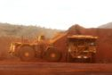An excavator loads ore into an autonomous dump truck at Fortescue Metals Group Ltd.'s Solomon Hub mining operations in the Pilbara region, Australia, on Thursday, Oct. 27, 2016. Shares in Fortescue, the world's No. 4 iron ore exporter, have almost trebled in 2016 as iron ore recovered, and the company cut costs and repaid debt. Photographer: Brendon Thorne/Bloomberg