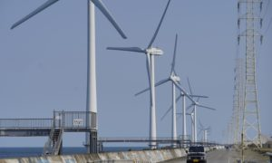 A vehicle drives past wind turbines operated by Wind Power Group KK in Kamisu, Ibaraki Prefecture, Japan, on Wednesday, April 29, 2020.Photographer: Toru Hanai/Bloomberg