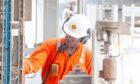 Worker in orange overalls checks equipment on FPSO