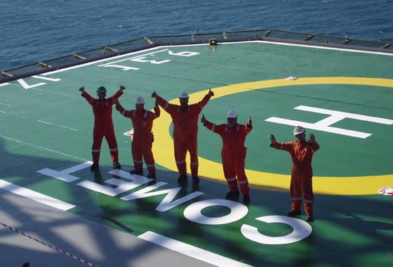 Five workers on a helipad waving