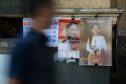 A man walks past calendars featuring images of Myanmar leader Aung San Suu Kyi in Yangon, Myanmar, on Monday, Dec. 18, 2017. Photographer: SeongJoon Cho/Bloomberg