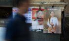 A man walks past calendars featuring images of Myanmar leader Aung San Suu Kyi in Yangon, Myanmar, on Monday, Dec. 18, 2017. Photographer: SeongJoon Cho/Bloomberg