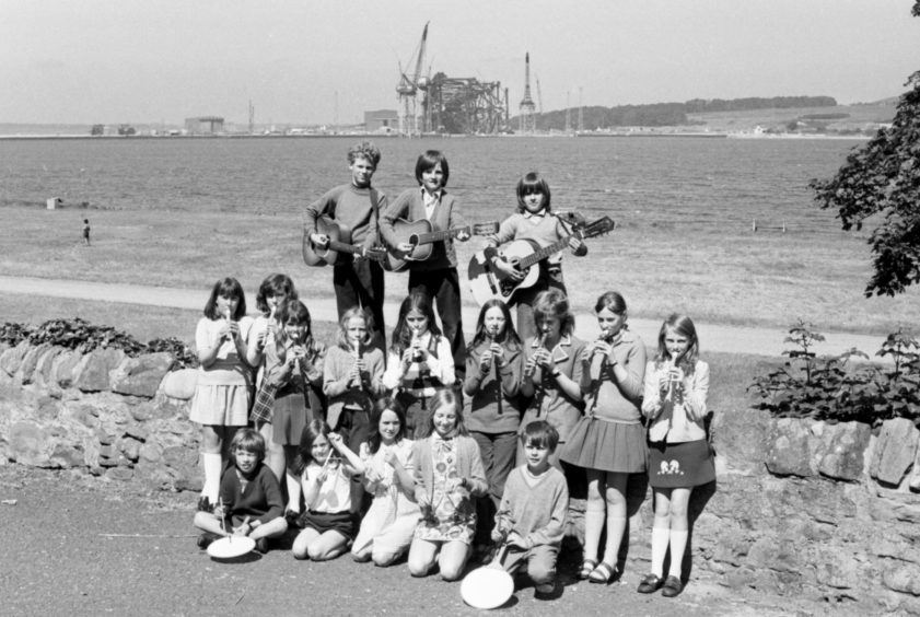 Members of the Cromarty School Orchestra, pictured with the oil rig construction at Nigg on the other side of the Firth in the background, in 1974.
