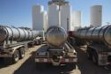 Tanker trucks sit in front of storage silos in Sunray, Texas, U.S., on Saturday, Sept. 26, 2020. After all the trauma the U.S. oil industry has been through this year -- from production cuts to mass layoffs and a string of bankruptcies -- many producers say they're still prioritizing output over reducing debt. Photographer: Angus Mordant/Bloomberg
