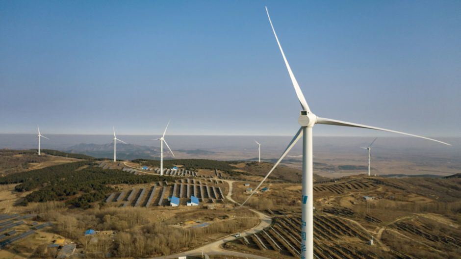 Wind turbines and solar panels on a hillside in China. Photographer: Qilai Shen/Bloomberg