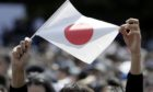 An attendee holds a Japanese national flag during a greeting ceremony with Japanese royal family at the Imperial Palace in Tokyo, Japan. Photographer: Kiyoshi Ota/Bloomberg