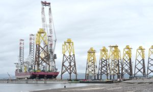 The large floating crane barge, Seajacks Scylla loads wind turbine base platforms at Nigg Energy Park for the Moray East offshore wind farm