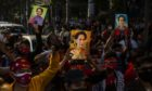 Demonstrators hold up images of Aung San Suu Kyi during a protest against Myanmar coup outside the Embassy of Myanmar in Bangkok, Thailand, on Monday, Feb. 1 2021. Photographer: Andre Malerba/Bloomberg