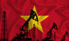 Silhouette of drilling rigs and oil derricks on the background of the flag of Vietnam.