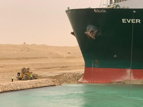 A small digger on the left, the prow of a large cargo ship on the right