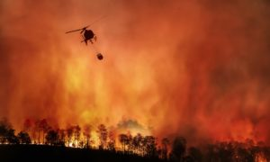 Fire fighting helicopter carry water bucket to extinguish forest fire in Indonesia: fire fighters have also been battling a blaze at the Cilacap oil refinery