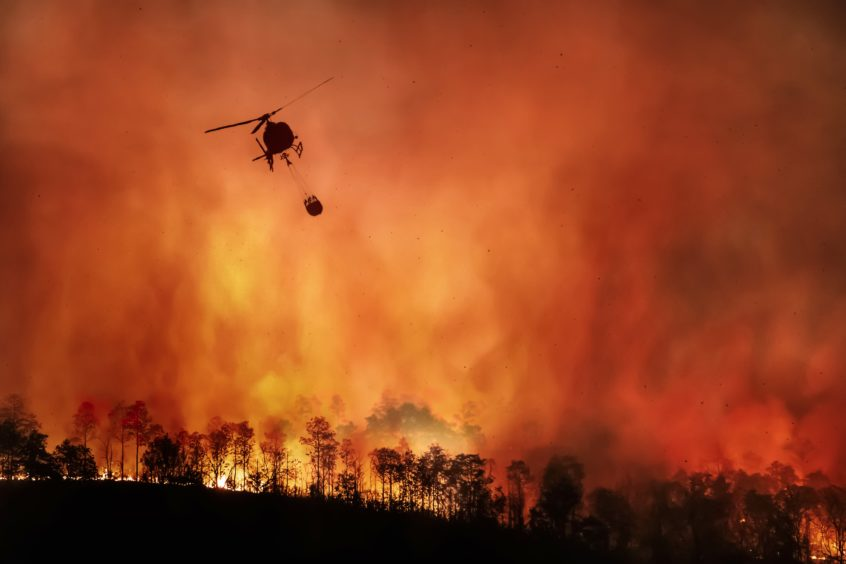 Fire fighting helicopter carry water bucket to extinguish forest fire in Indonesia: fire fighters have also been battling a blaze a the Balongan oil refinery