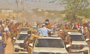 President Deby in a car driving through dusty road in Mao, Chad