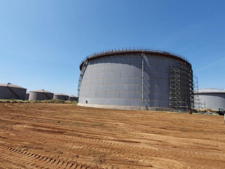 A storage tank in a dusty field, with scaffolding