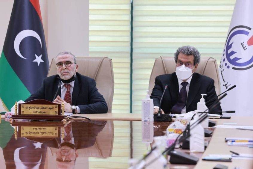 Two men sit at meeting table with Libyan flag