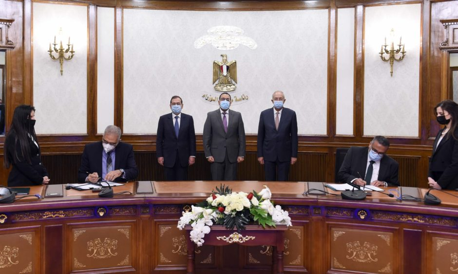 Three men in suits watch two men in suits sign deal