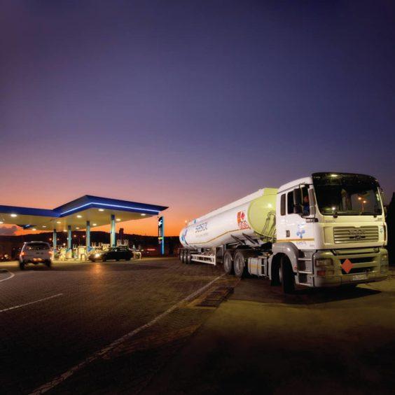 A Sasol fuel tanker leaves a fuel station at dusk