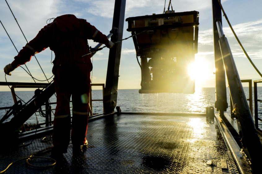 Silhouette of worker recovering robotics Remote Operated Vehicle (ROV) after entering sea surface during oil and gas pipeline inspection.