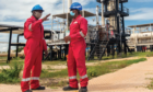 Two workers in Tanzania's Mnazi Bay dressed in red overalls