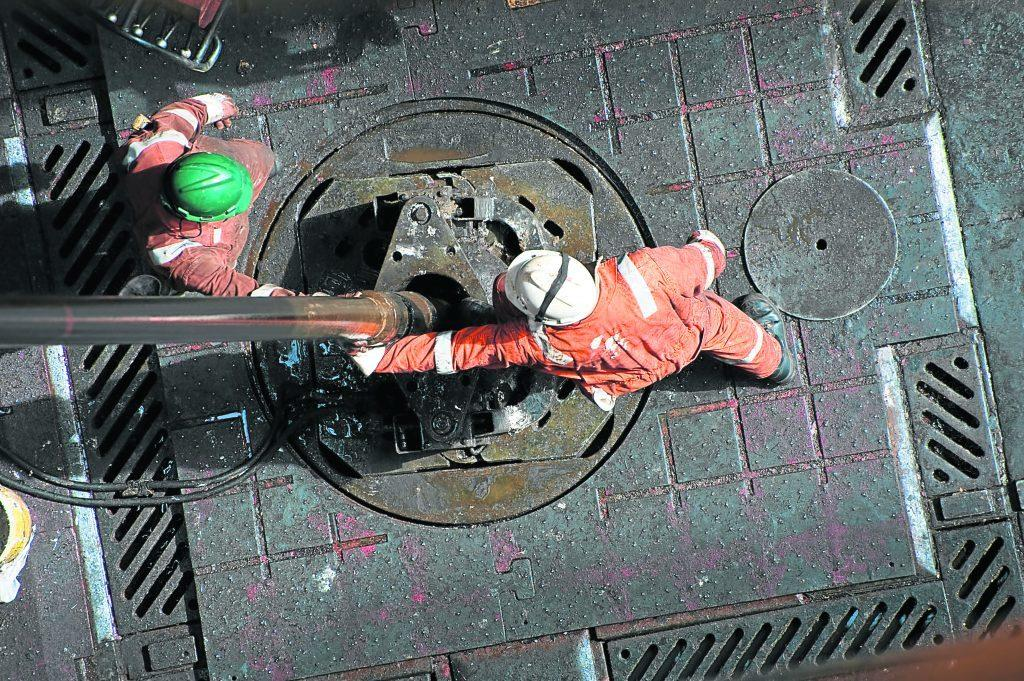 Two workers with hard hats on a drilling platform