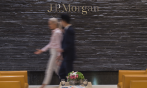 Two blurry people walk in front of wall saying JP Morgan