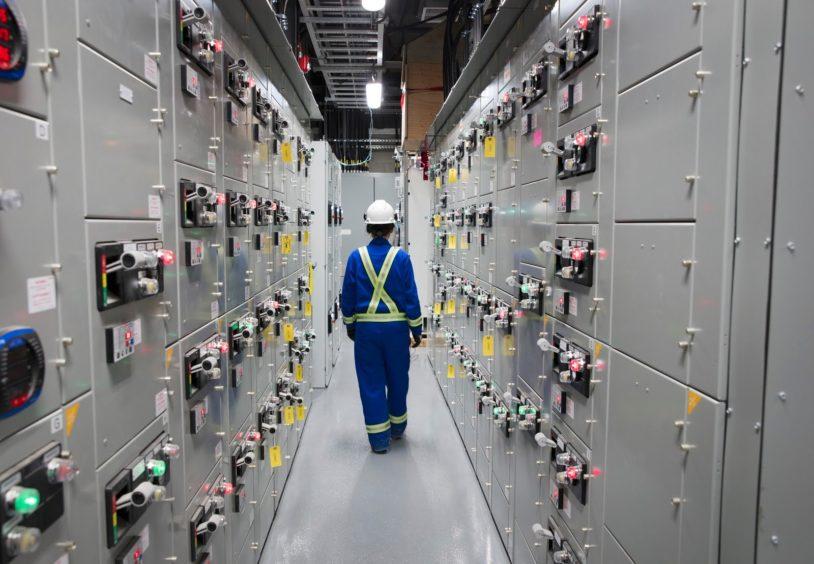 Worker in blue overalls walks away between electrical equipment