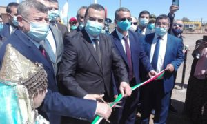 Group of men in suits, one cutting a ribbon,