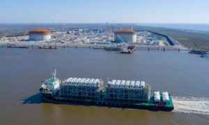 A ship carrying LNG equipment moves along a waterway