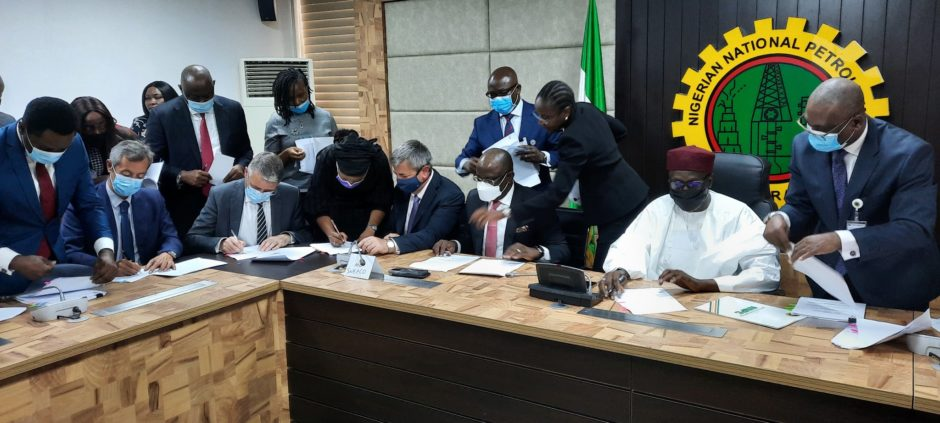 Men in suits sit at a table signing documents, with NNPC logo behind