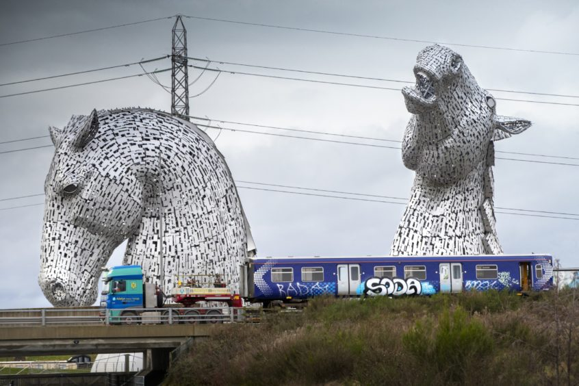 : Converted rolling stock to be used in the Scottish hydrogen trains project is driven past The Kelpies horse sculptures near Falkirk