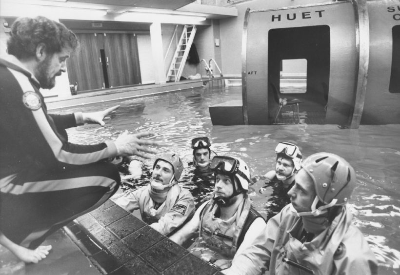 """Senior Instructor Angus Macdonald briefs his pupils on how to swim clear from an upturned vessel."""" Picture taken 3 December 1980."""