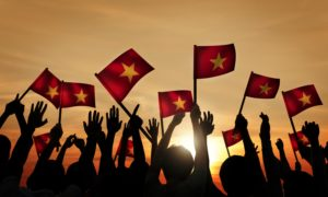 A group of people waving Vietnamese flags. The Southeast Asian country hopes to progress the Block B gas project.