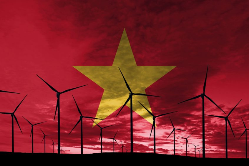 Vietnamese wind farm at sunset against the Vietnam flag.