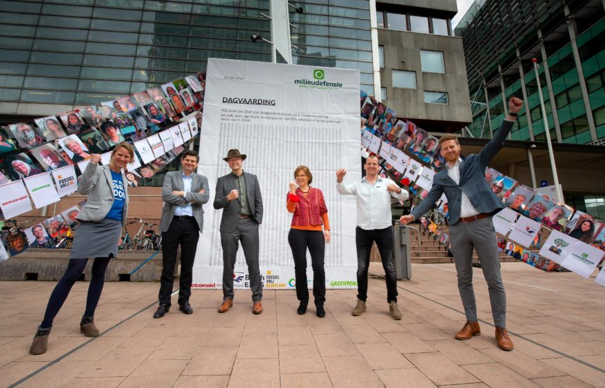Six people stand on a pavement holding pictures, with a poster behind