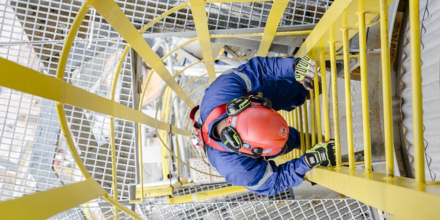 Top down shot of a man climbing down a ladder.
