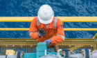 An offshore worker examining a valve