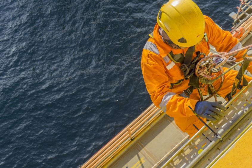 Oil worker climbs ladder offshore