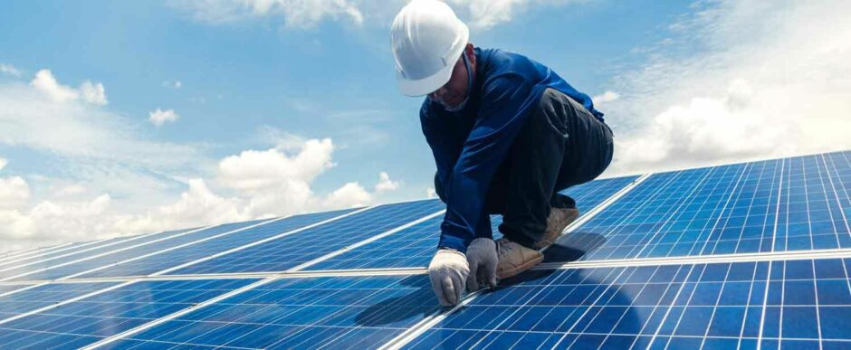 Man in hard hat stands on solar panel
