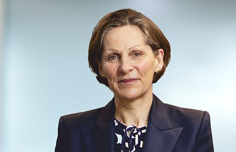 A woman wearing a jacket against a grey background