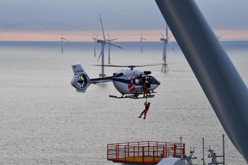 A worker being winched onto an offshore wind turbine.