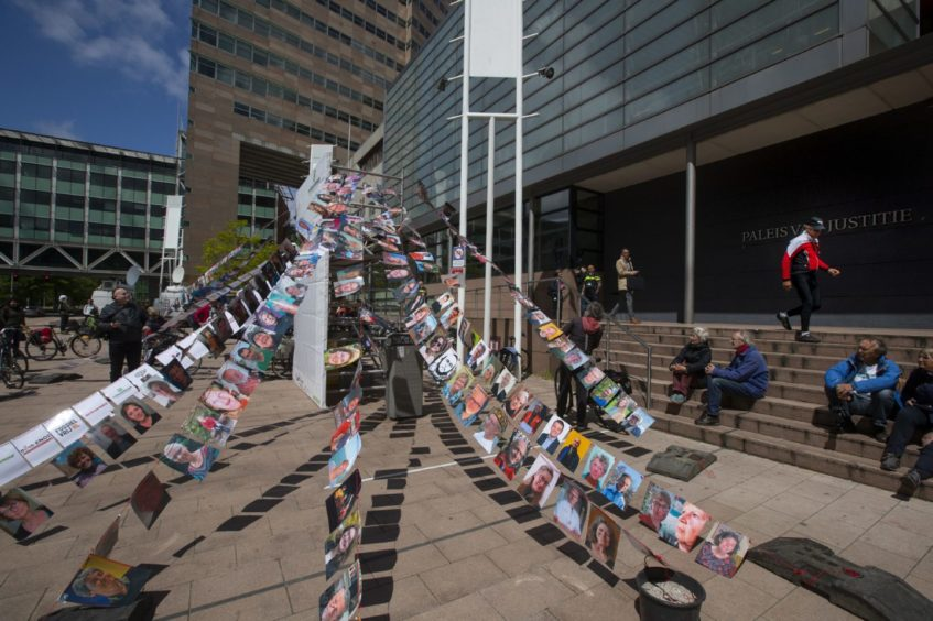 Pictures of plaintiffs fly outside the court where Milieudefensie, the Dutch arm of the Friends of the Earth environmental organization, took Shell to court, in The Hague, Netherlands, Wednesday, May 26, 2021. (AP Photo/Peter Dejong)