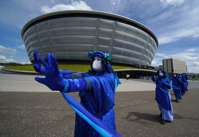 Extinction Rebellion Scotland's Blue Rebels perform outside the SEC Armadillo in Glasgow, where the global climate change conference Cop26 will take place in November: Andrew Milligan/PA Wire