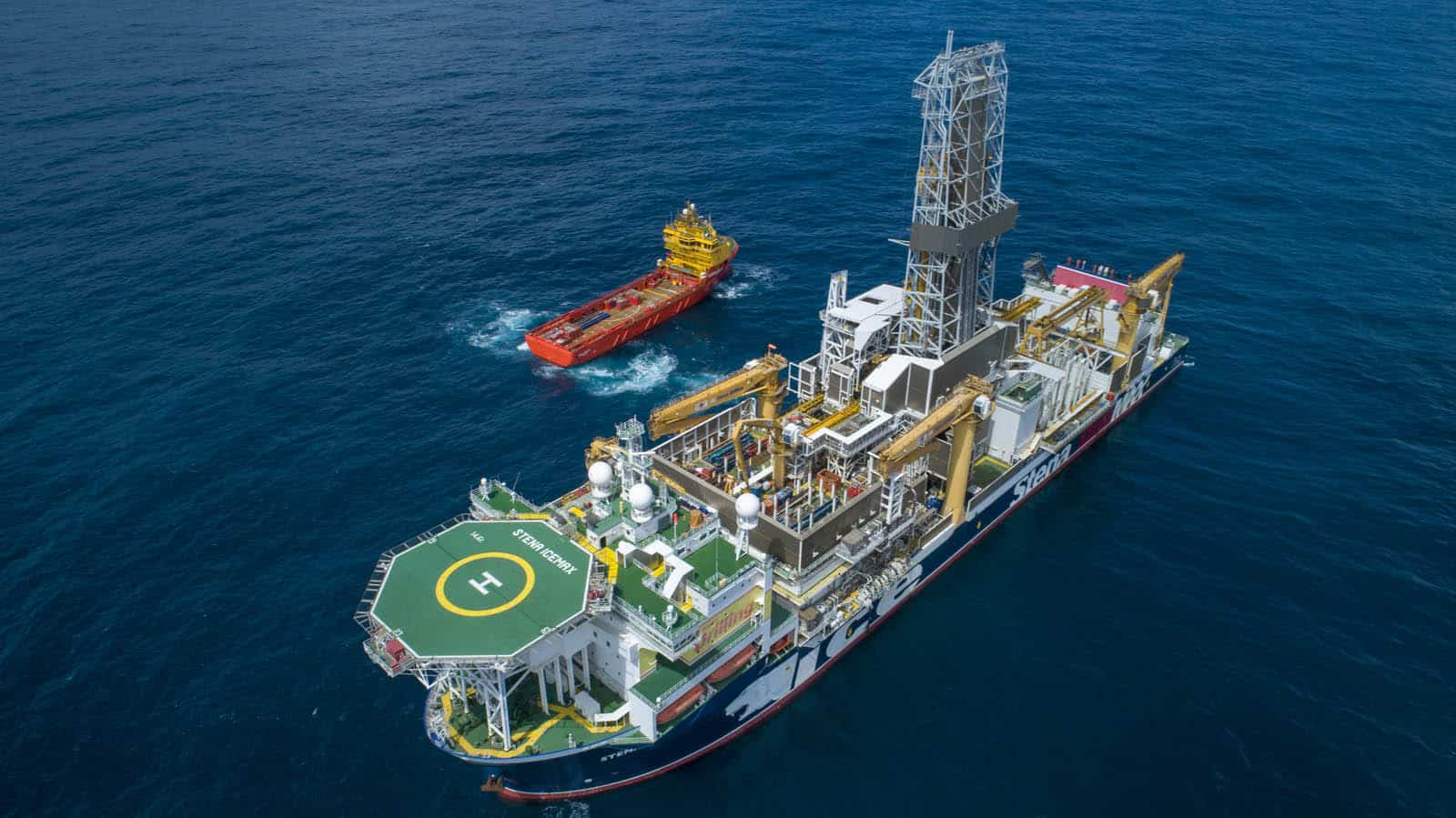 A drilling rig in the foreground with a smaller vessel behind